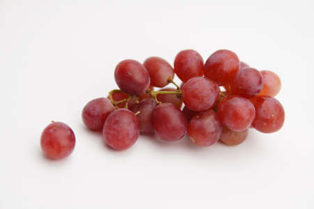 Fresh and ripe red grapes isolated in white background. Bunch of raw and juicy grapevines .. Stock Photo