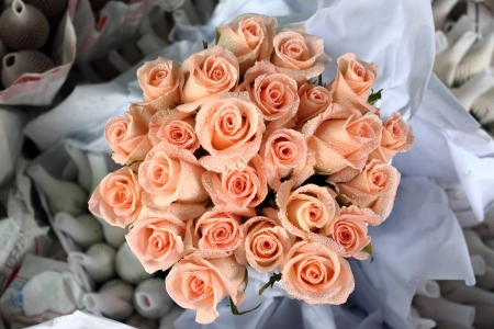 Roses with droples are wrapped in paper bouquet ready for selling  photo