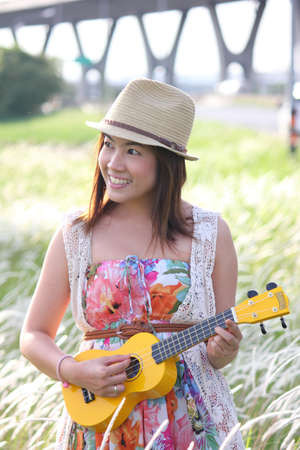 A cheerful asian girl with her ukulele in a meadow Stock Photo