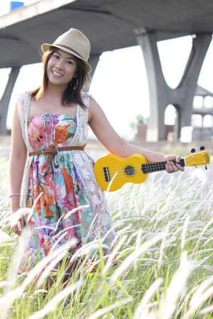 A cheerful asian girl with her ukulele in a meadow photo