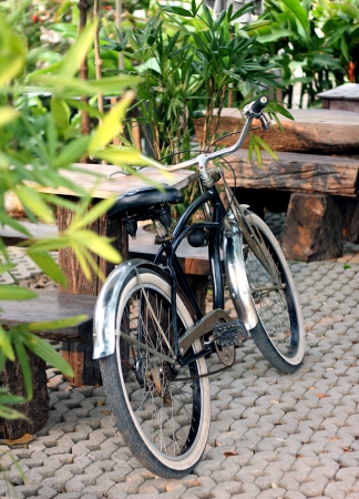 a black bicycle leaning against wooden table photo