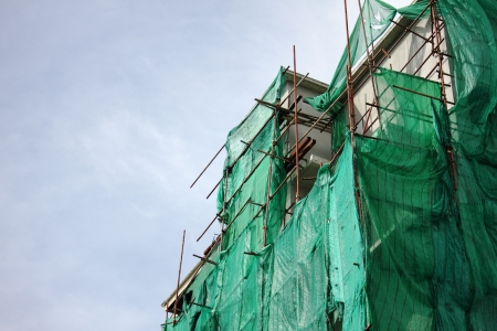 tarpaulin: building wrapped in tarpaulin for safety ducting construction Stock Photo