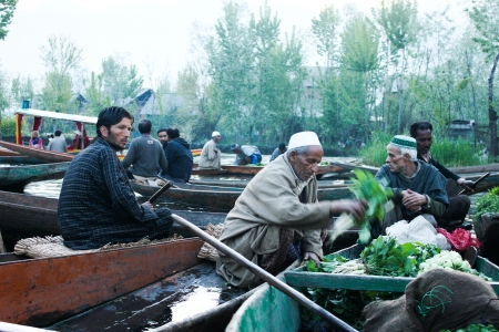 KASHMIR,INDIA- APRIL 19:Atmosphere in the morning at traditional floating vegetable market  where local people buy, sell and sometimes exchange vegetables  in Dal Lake, Srinagar, Kashmir, INDIA on April 19, 2012
