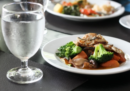 grilled meat with broccoli and carrot on white plate and a glass of water on black table