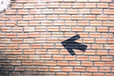 black arrow on brick wall background photo