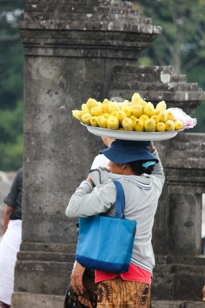 pilgrim costume: 2012 in Bali, BALI – OCTOBER 17: Unidentified village women carry offerings of food baskets on their heads and pilgrims coming out from Besakih temple in October 17, Indonesia. Editorial