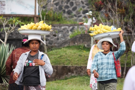 pilgrim costume: 2012 in Bali, BALI – OCTOBER 17: Unidentified village women carry offerings of food baskets on their heads and pilgrims coming out from Besakih temple in October 17, Indonesia.