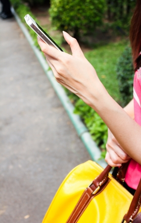 woman hand holding smartphone with street background photo