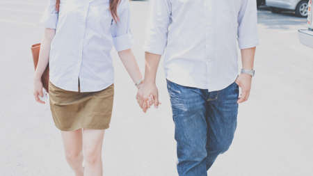 Closeup of young affectionate couple holding hands over white background. Stock Photo