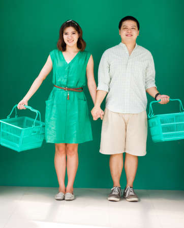 asian couple holding empty supermarket cart photo