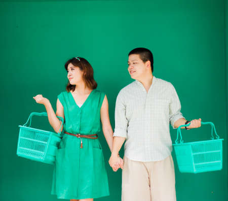 shopping basket: asian couple holding empty supermarket cart