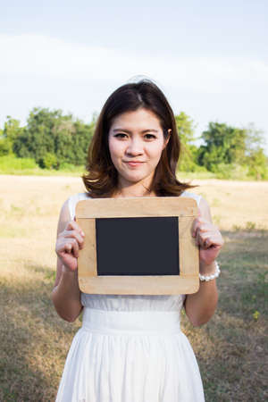 beautiful woman in white dress holding blank blackboard photo