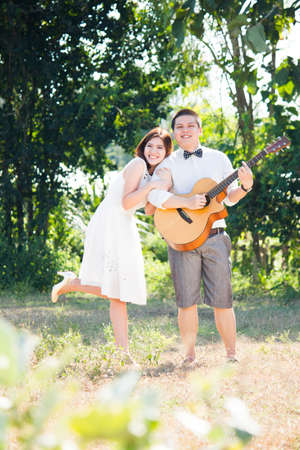 Portrait of  romantic Asian young couple playing a guitar in a park photo