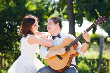 Portrait of  romantic Asian young couple playing a guitar in a park Stock Photo