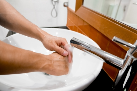 washing hands under running tap water photo