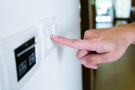 hands off: hand with finger on light switch, about to turn off the lights  Stock Photo