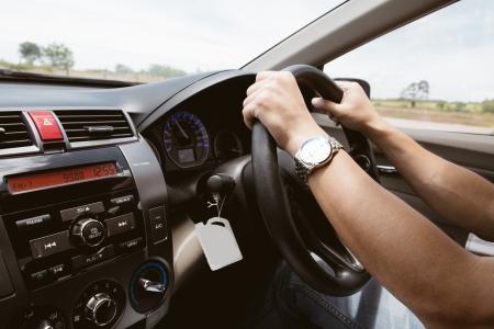 mannelijke handen op het stuurwiel aan de rechterkant met land zijaanzicht