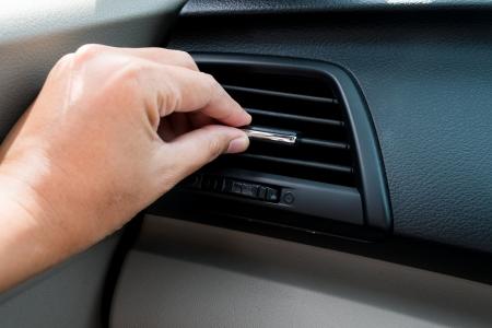 air: hand adjusting air conditioner in car