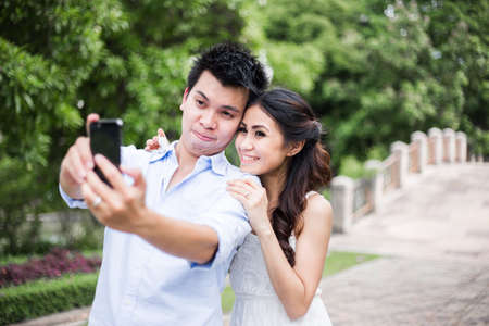 yong asian couple taking photo using telephone camera in park photo