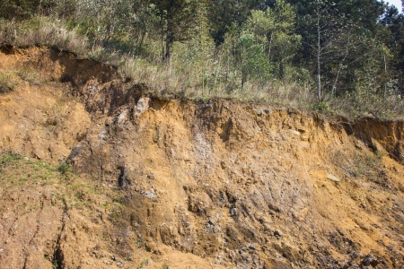 clay stone road in jungle: cracked mountain showing red soil Stock Photo