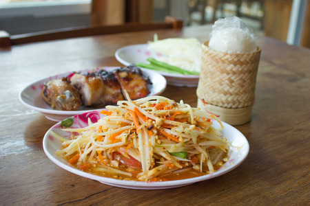 som tum Thai with sticky rice and grilled chicken on wooden table Stock Photo