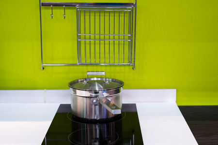 green modern kitchen  and stainless steel pot on induction electric hob Stock Photo