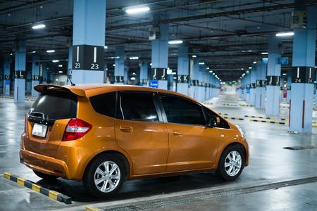 eco car in big empty indoor parking garage at night