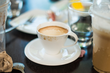 dessert plate: Tazza di caff� espresso Messy  macchiato circondato da piatto da dessert e ghiacciato bicchieri di plastica di caff� sul tavolo del caff�