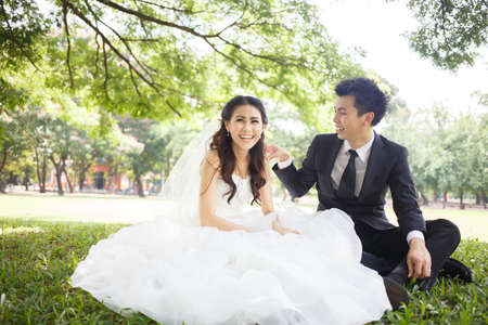 happy asian couple in wedding dress in a green park