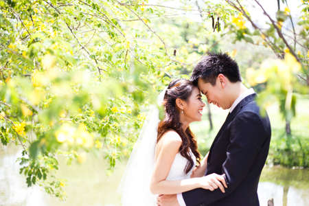 happy asian couple in wedding dress in a green park photo