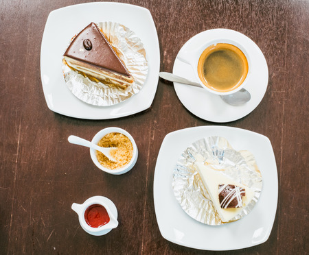top view of hot coffee, sugar, cakes and desserts on wooden table photo