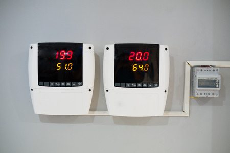 Digital thermometer and humidity meter on wall with air conditioner