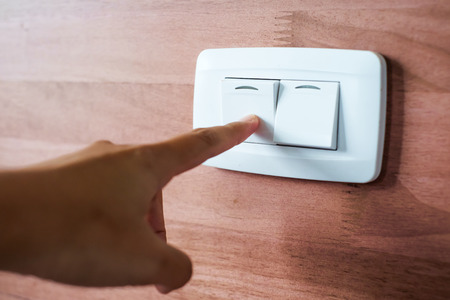 Turning off  on wooden wall-mounted light switch - energy saving concept photo