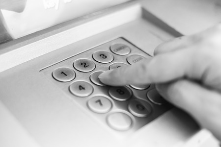 hand pressing ATM keyboard photo