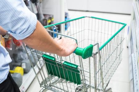 male hand pushing shopping cart at supermartket photo