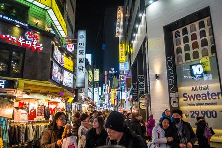 서울, 한국 - 2014 년 12 월 7 일 : 밤에 명동 지구에서 신원을 알 수없는 사람들. 명동은 하이 엔드 패션 아울렛, 코스메틱 및 거리 음식으로 유명한 서울