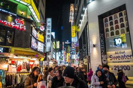 SEOUL, SOUTH KOREA -DECEMBER 7, 2014: Unidentified people at Myeong-Dong district at night. Myeongdong is one of Seoul's main shopping districts, famous for hi-end fashion outlet, cosmatics and street food.
