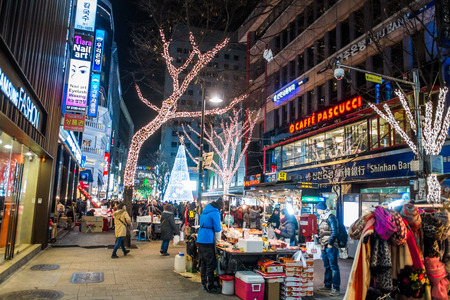 east end: SEOUL, SOUTH KOREA -DECEMBER 7, 2014: Unidentified people at Myeong-Dong district at night. Myeongdong is one of Seouls main shopping districts, famous for hi-end fashion outlet, cosmatics and street food.