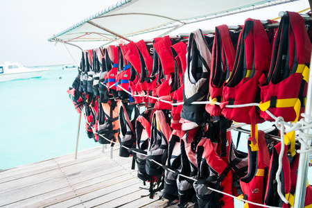 emergency vest: rows of hanging life jackets with sea background Stock Photo