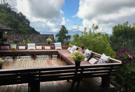 outdoor living: outdoor living room or balcony with pillows with mountain and forest background - home decoration