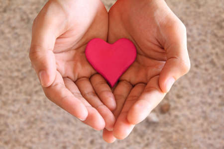 dar un regalo: Sosteniendo el coraz�n rojo sobre fondo de arena Foto de archivo