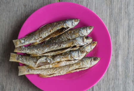 Fried, mullet, fishes in pink plastic dish on old wood floor. Standard-Bild