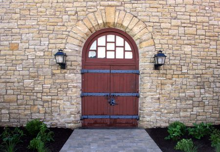 gateway arch: rustic wood doors fill this stone archway in a classic rustic stone building.