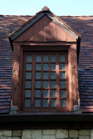 filtered light falls on this classic wood dormer on top of this stone building Stock Photo - 5405782