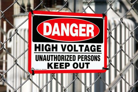 keepout: warning sign posted on the fence surrounding large electrical transformers.