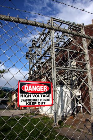 warning sign posted on the fence surrounding large electrical transformers. Stock Photo - 5405836
