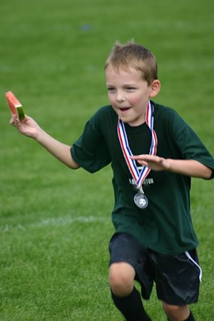 Kid with medal and watermellon after winning game Stock Photo
