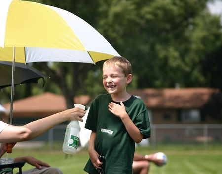 Kids gets sprayed down during soccer game on a hot day photo