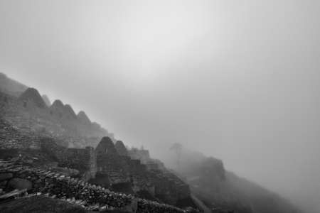shrouds: A layer of morning fog shrouds the ancient city of Machu Picchu in mystery. Stock Photo