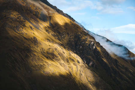salkantay: A rocky mountain side covered in shadow and clouds on the Salkantay Trail in Peru.